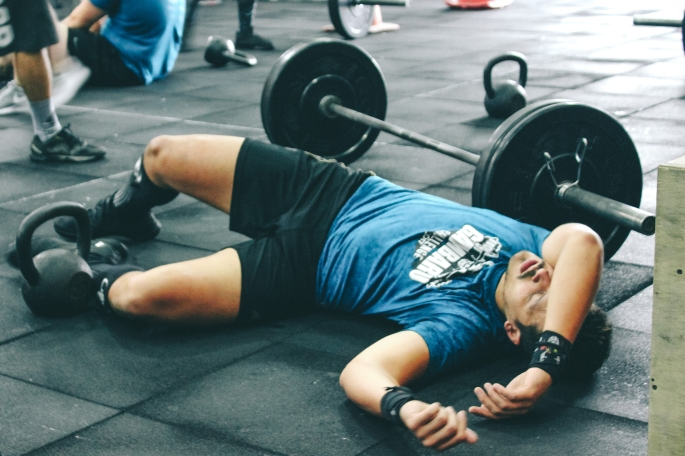 Canva-Man-Lying-on-Rubber-Mat-Near-Barbell-Inside-the-Gym